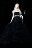 Modefors av den härliga blonda kvinnan i en lång svart klänning Fotografering för Bildbyråer