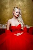 Modefors av den härliga blonda kvinnan i ett långt svart klänningsammanträde på soffan Royaltyfria Foton