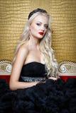 Modefors av den härliga blonda kvinnan i ett långt svart klänningsammanträde på soffan Arkivfoto