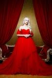 Modefors av den härliga blonda kvinnan i ett långt svart klänningsammanträde på soffan Fotografering för Bildbyråer
