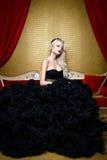 Modefors av den härliga blonda kvinnan i ett långt svart klänningsammanträde på soffan Royaltyfri Fotografi