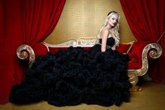 Modefors av den härliga blonda kvinnan i ett långt svart klänningsammanträde på soffan Arkivbilder