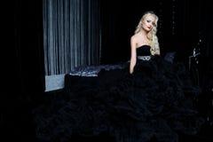 Modefors av den härliga blonda kvinnan i ett långt svart klänningsammanträde på soffan Royaltyfri Foto