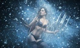 Modefors av en sexig kvinna i damunderkläderinnehavstearinljus Arkivfoton