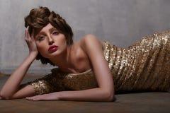 Modefoto av den härliga flickan som bär den lyxiga guld- klänningen Arkivbild
