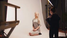 Modefotobühne hinter dem vorhang - das blonde hübsche Mädchen, das für Fotografen aufwirft - Modell sitzt an den Knien Stockfotos