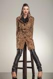 Modefrau, die auf einem Schemel sitzt Lizenzfreie Stockfotografie