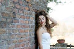 Modefrau, die an der Backsteinmauer sich lehnt Stockfoto