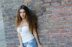 Modefrau, die an der Backsteinmauer sich lehnt Lizenzfreies Stockbild