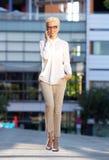 Modefrau, die am Handy geht und spricht Stockfoto