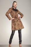 Modefrau im Tierdruckmantel, der für die Kamera aufwirft Lizenzfreie Stockfotografie