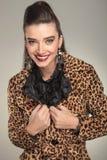 Modefrau im Tierdruckmantel, der ihren Kragen repariert Stockbild