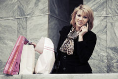 Modefrau mit Einkaufstaschen um Handy ersuchend Lizenzfreie Stockfotografie