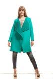 Modefrau in voller Länge im grünen Mantel Stockfotografie