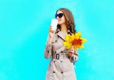 Modefrauen-Getränkkaffee von der Schale hält gelbe Ahornblätter des Herbstes lizenzfreie stockfotografie