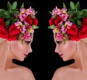Modefrisur. Mädchen mit Rosen. schöne junge Frau mit Blumen in ihrem Haar über Schwarzem Lizenzfreies Stockfoto