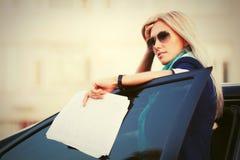 ModeGeschäftsfrau in der Sonnenbrille nahe bei ihrem Auto Stockbild