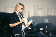 ModeGeschäftsfrau in der Sonnenbrille nahe bei ihrem Auto Lizenzfreie Stockfotos