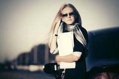 ModeGeschäftsfrau in der Sonnenbrille nahe bei ihrem Auto im Freien Stockbild