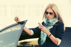 ModeGeschäftsfrau in der Sonnenbrille unter Verwendung des Handys neben einem ihrem Auto Lizenzfreie Stockbilder