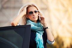 ModeGeschäftsfrau, die um das Telefon durch ihr Auto ersucht Stockfotos