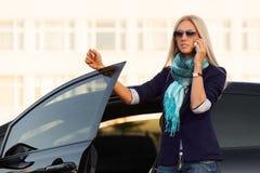 ModeGeschäftsfrau, die um Handy durch ihr Auto ersucht Lizenzfreies Stockfoto