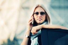 ModeGeschäftsfrau, die um Telefon durch ihr Auto ersucht Lizenzfreie Stockfotografie