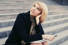ModeGeschäftsfrau mit dem Notizbuch, das auf den Schritten sitzt Lizenzfreie Stockfotografie