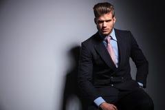 ModeGeschäftsmann im Anzug und in der Bindung sitzt Stockfotografie