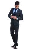 ModeGeschäftsmann-UNO, die seine Klage knöpft und unten schaut stockfotografie