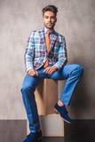 ModeGeschäftsmann, der auf hölzernen Kästen sitzt Stockfotografie
