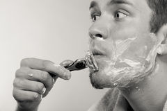 Młodego człowieka golenie używać żyletkę z śmietanki pianą Zdjęcie Royalty Free