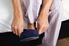 Młodego człowieka kładzenie na jego kapciach Zdjęcie Royalty Free