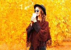 Modeherbstfrau trinkt Kaffee im schwarzen runden Hut, gestrickter Poncho lizenzfreie stockbilder