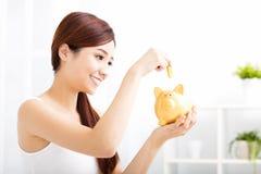 młodej kobiety oszczędzania pieniądze w prosiątko banku Zdjęcia Stock