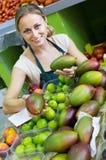 Młodej kobiety sprzedawania mango przy rynkiem Zdjęcie Stock