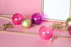 Modejulprydnader på ram och pärlor för rosa bakgrund guld- Royaltyfri Fotografi