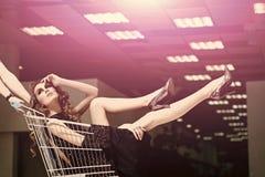 Modeköp Flickan i den trendiga klänningen, skor i spårvagn shoppar in Royaltyfri Bild