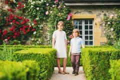 Modekinder, die im schönen Garten aufwerfen Lizenzfreie Stockbilder