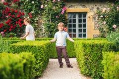 Modekinder, die im schönen Garten aufwerfen Stockfotos