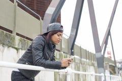 Modekvinna med baseballmössan som ser meddelandet hennes smarta telefon i gatan Arkivbild