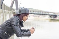 Modekvinna med baseballmössan som ser meddelandet hennes smarta telefon i gatan Fotografering för Bildbyråer