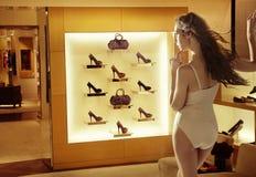 Modekvinna som ser hög-häl skor arkivbild