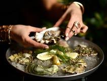 Modekvinnahänder med dyra guld- cirklar tar ostron arkivbild