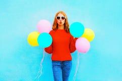 Modekvinnan gör en luftkyss med färgrika ballonger på blått Arkivfoto