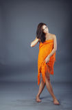 Model. Studio photo of the nifty shoeless lady covered by orange fabric stock images