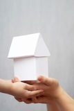 Model. A model of a house in hands Royalty Free Stock Photos