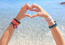 Model advertising greek jewelry on the beach - creating heart symbol with her hands Royalty Free Stock Images
