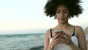 Model with afro hairstyle hear music on the beach stock video
