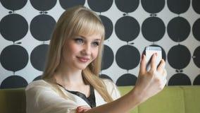 Model aged 20s making selfie photo. Beautiful model aged 20s making selfie photo using a smartphone at the beauty salon stock footage